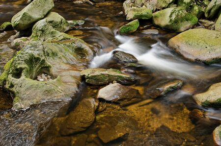Detail of small beautiful cascade between mossy stones.  photo