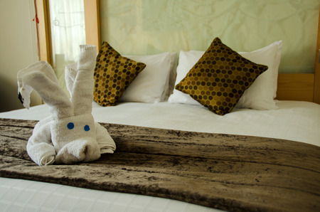 White brown bedroom with white plush toy on the brown bed cover. photo