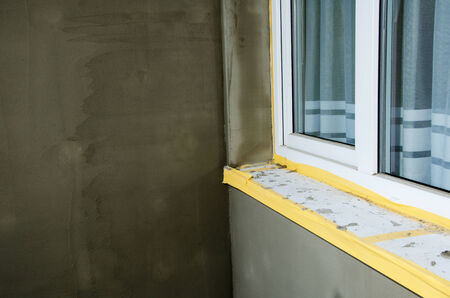 balcony window: Semifinished repairing of balcony, gray plaster and dirty white window. Stock Photo
