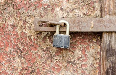 Old rusty padlock on damaged wooden doors surface. photo