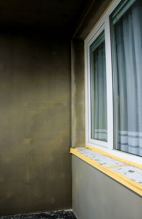 semifinished: Semifinished repairing of balcony, gray plaster and dirty white window. Stock Photo