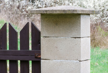 Concrete blocks side post of brown wooden fence. photo