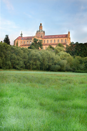 cited: Baroque monastery at the top of small hill.