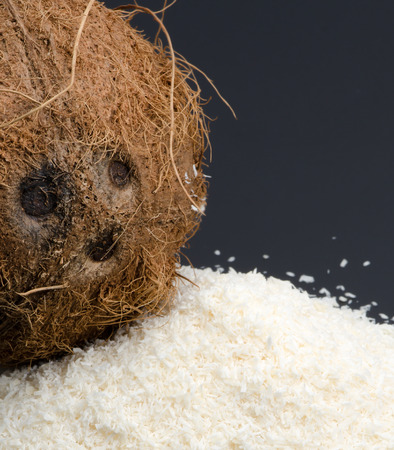 desiccated: Heap of desiccated coconut and whole coconut isolated on black background. Stock Photo