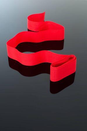 gradual: Cinta roja encrespada aislada en negro fondo blanco gradual, elegante s�mbolo de celebraci�n.