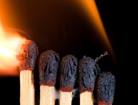 Close-up of five burning matches on black background. photo