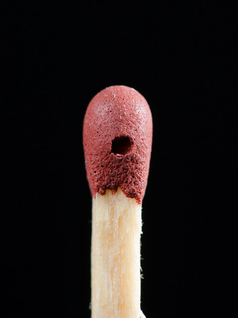 match head: Detail of damaged red match head isolated on black backgroudn.