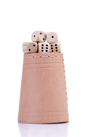 double the chances: Five wooden dice on the leather dish. Stock Photo