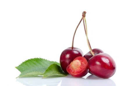 cereza: Three and one cutted cherries next to leaves. Foto de archivo