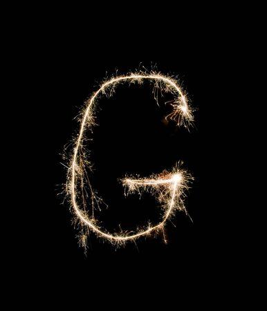 g alphabet: Letter G drew with spakrs on a black background.