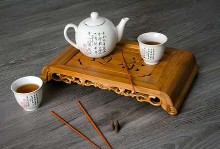 antique table: Exotic tea still-life contains teapot, cups, insence and tea sea. Stock Photo