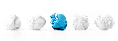 smashed: Blue paper ball between four white ones as a symbol of difference and variety of society and ideas.