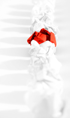 paper wad: Red paper ball among white ones as a symbol of difference, autonomy and independence. Stock Photo