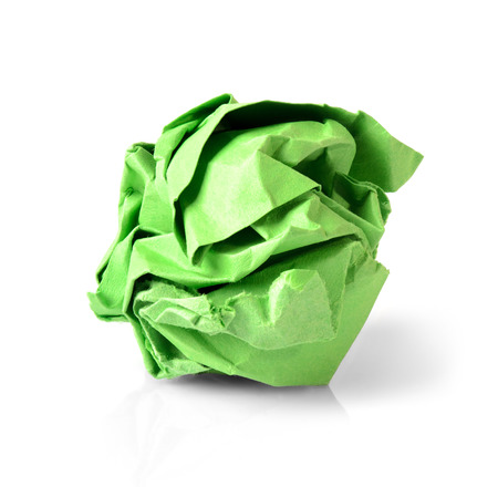 Green wrinkled paper ball isolated on white background, symbol of recycling and wasting our resources.