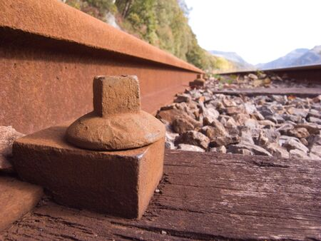 Close-up of bolt fixing the line and sleeper of a railway.
