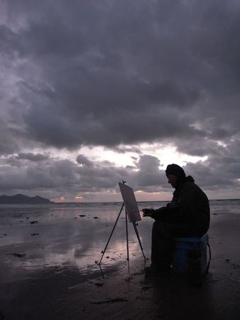 Silhouette of an artist at sunset in overcast windy weather.