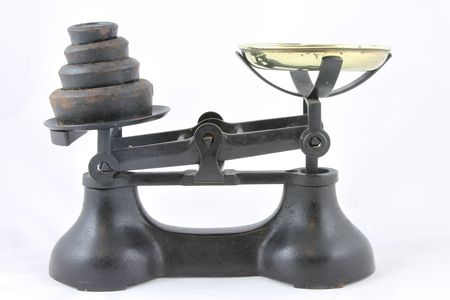 Antique weighing scales with brass bowl and rusty black weights.