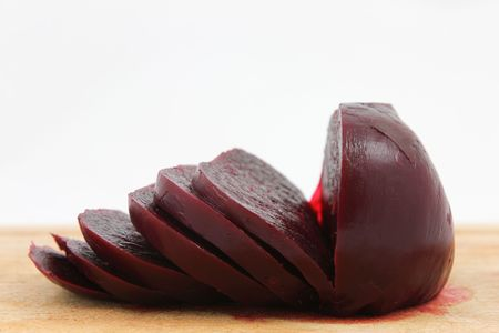 Cooked beetroot sliced on chopping board against a white background.