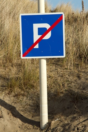 No parking sign, square shaped with the letter P in white on a blue background with a diagonal red line. The sign is attached to a poll and situated in sand with grasses. Stock Photo