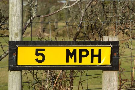 mph: Yellow sign showing 5 MPH attached to wooden posts with a fence.