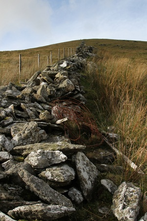 tumble down: Tumble down stone wall with rusty barbed wire and a new fence adjacent with posts running up a hillside.