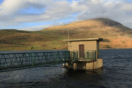 Water storage facility, a reservoir, under a hill. a bridge leads to the access building. Stock Photo