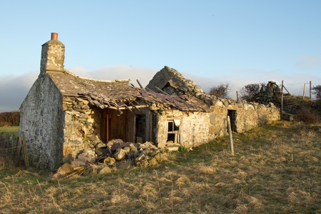 Derelict abandoned building, cottage, with crumbling walls and roof on grass with a blue sky. Stock Photo