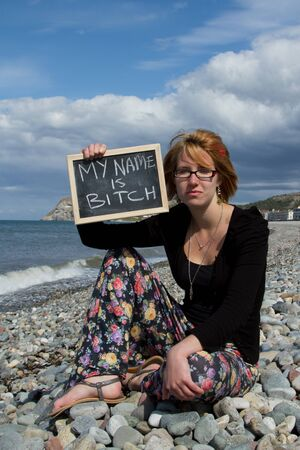 bitch: A pretty young woman sits on a pebble beach with a sign with the words my name is bitch. Stock Photo