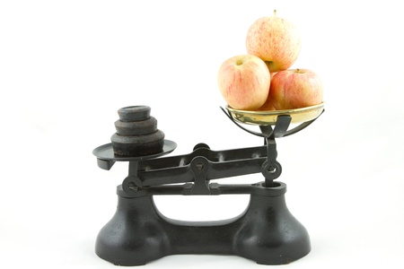 An old weighing scales painted black with a brass bowl containing apples all isolated on white.