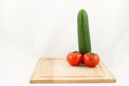 phallic: A wooden chopping with a phallic combination of cucumber and tomato isolated on white. Stock Photo