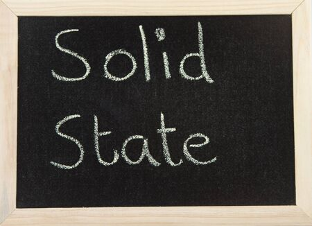 solid state: A black board with a wooden frame and the words SOLID STATE written in chalk.