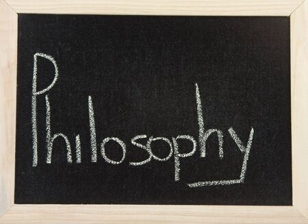 A black board with a wooden frame and the words PHILOSOPHY written in chalk. Stock Photo