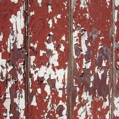 Wooden tongue and groove panels with red, green and white coats of flaking paint. Stock Photo