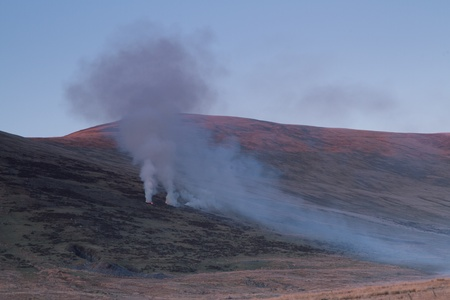 land management: Hillside in the evening light with smoke coming from gorse fires during land management. Stock Photo