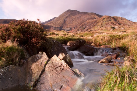 A stream in the foreground leads to the Welsh mountain peak Moel Siabod situated in the Snowdonia National park.