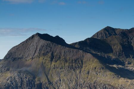north ridge: The east face and north ridge of Crib Goch with mount Snowdon in the distance, located in the Snowdonia National Park, Wales, UK. Stock Photo