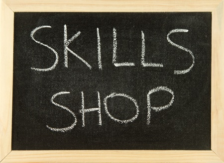 shop skill: The words SKILL SHOP hand written in white chalk on a black board with a wooden frame. Stock Photo