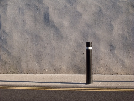 A painted uneven rendered wall with a slab pavement and post and double yellow lines in front. Stock Photo - 11961259