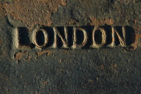 The name of the UK capital, LONDON, raised in metal on metal with rust and chipped black paint.