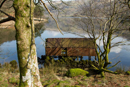 A rusty metal derelict boathouse in the trees on the shore of a lake. Stock Photo