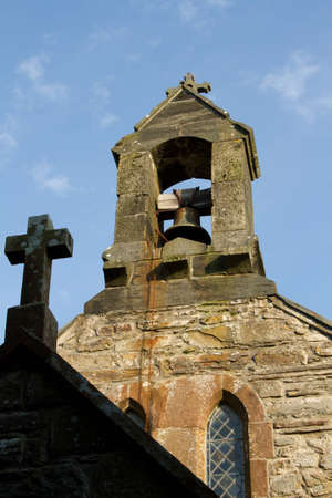 A shaded cross leads to a church bell tower with bell and chain backed by a blue sky. Stock Photo - 12757296