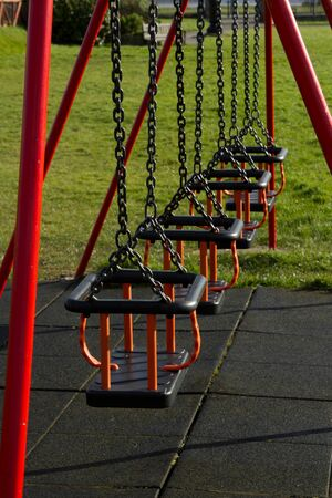 padded: A row of swing seats on metal chains with safety bars and a protective padded floor.