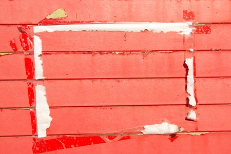 flaking: Wooden horizontal slats painted red with areas of flaking paint and a framed area with a paper and tape surround. Stock Photo