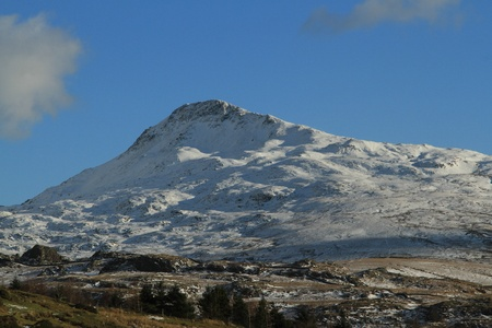 The snow covered peak of Yr Aran, Snowdonia National park, Wales, UK, against a blue sky with cloud. Stock Photo
