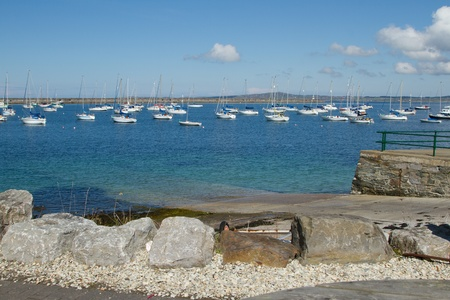 Large marina area at Holyhead, Wales, UK, with yachts moored in the water with a slipway and breakwater in the distance