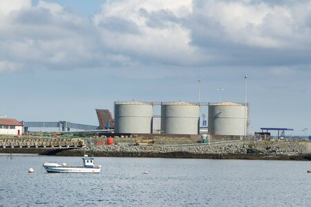 A dock with walkways and three large metal storage tanks with a boat in the sea and a cloudy sky. Stock Photo