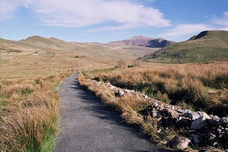 A footpath leads through moorland towards mount Snowdon, Snowdonia National park, Wales, UK, with a blue sky and cloud in the distance. Stock Photo