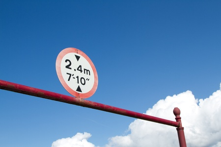A circular sign indicating height restriction in black on a white background with red edgeing on a red bar and post against a blue sky with clouds.
