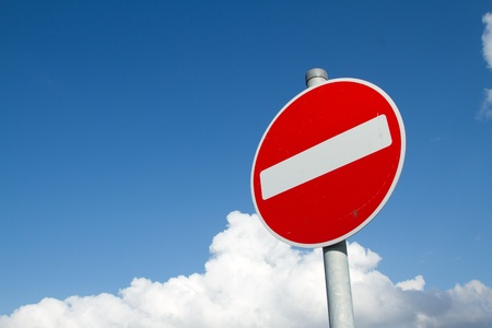 metal post: A circular red sign with a white bar indicating NO ENTRY on a grey metal post against a blue cloudy sky. Stock Photo