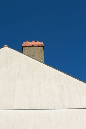 A pale coloured gable end with a chimney with ornate red brick against a blue sky. Stock Photo
